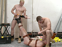 Muscular construction workers keep a sub bound naked