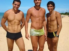 Big muscled dudes are wearing tight trunks at the beach